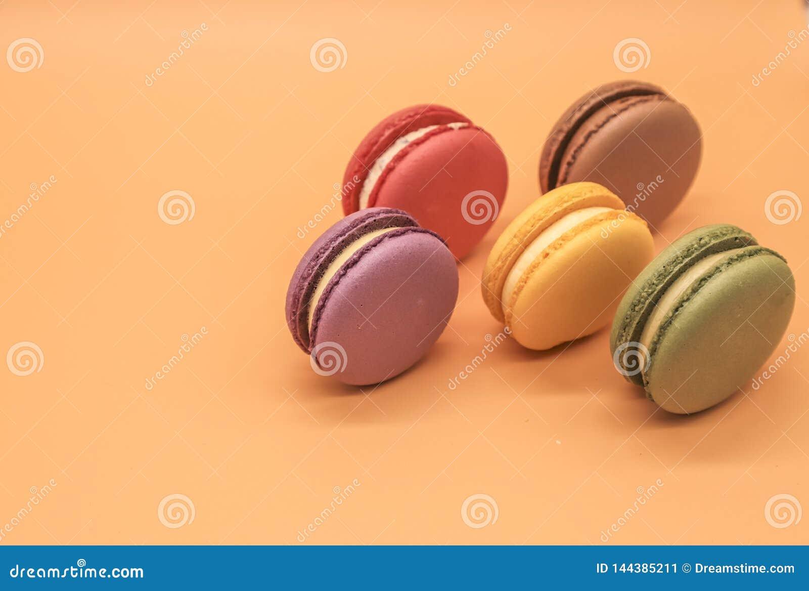 Colorful macaroons cakes on orange background
