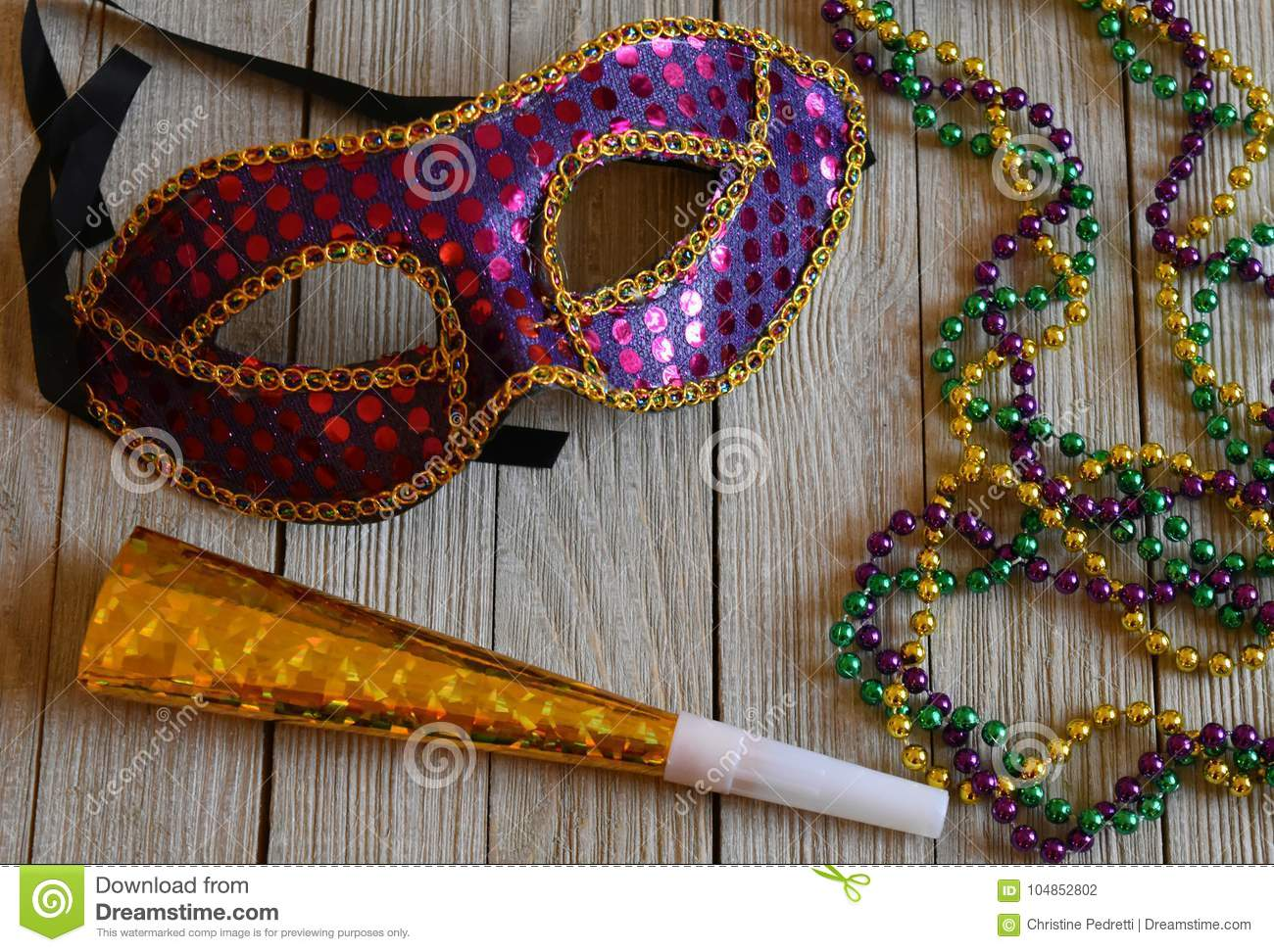 Colorful Mardi Gras mask with beads on wood background