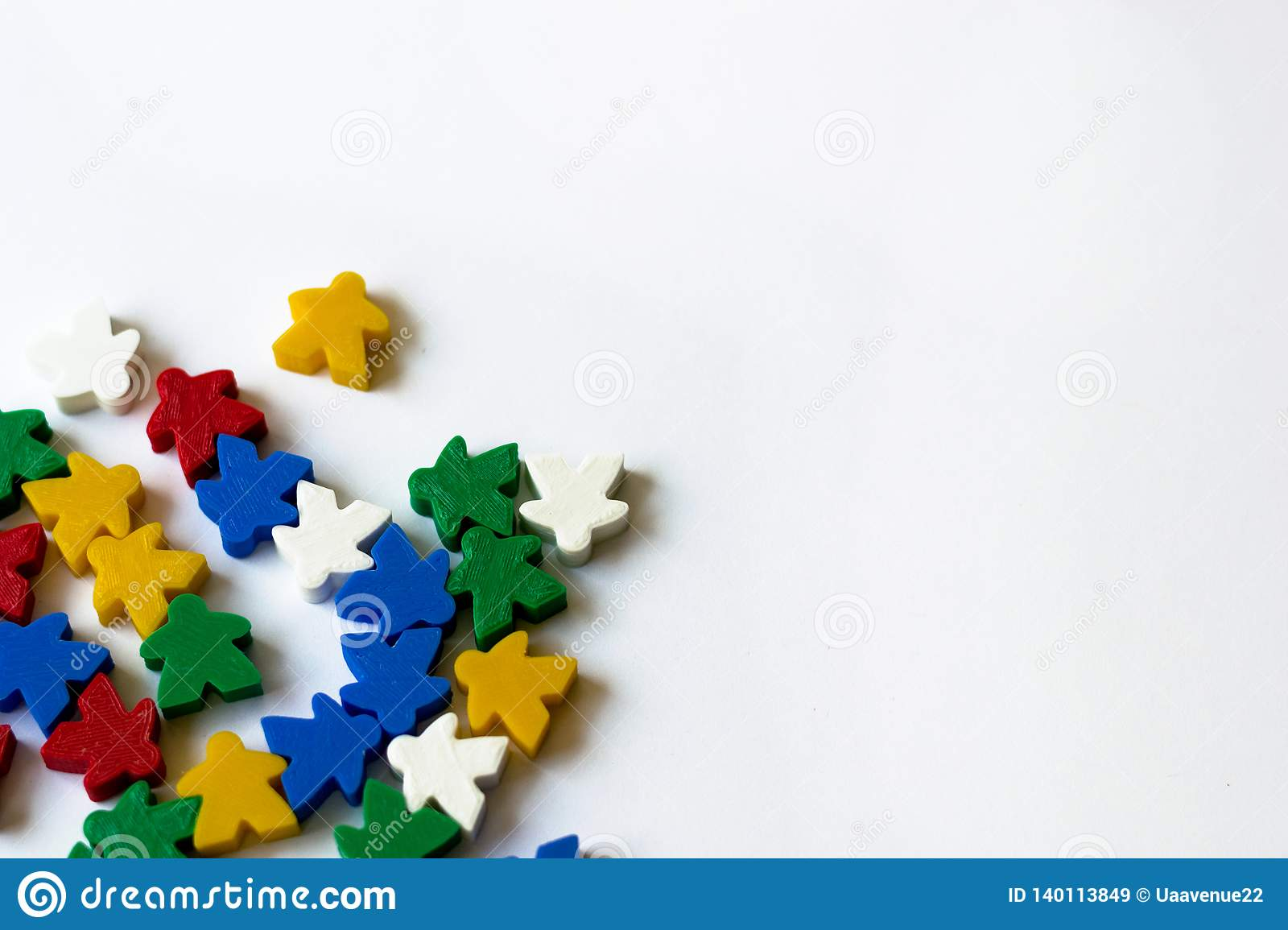 Colorful meeples as components of board game on white background with copyspace. Concept of party game playing, leisure, fun,