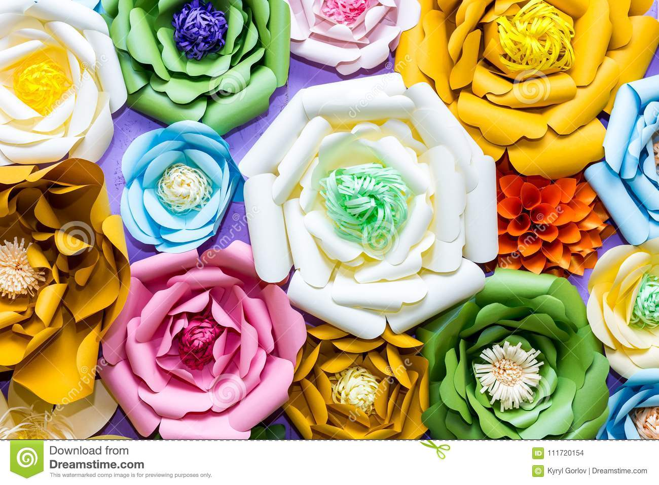 Colorful paper flowers on wall. Handmade artificial floral decoration. Spring abstract beautiful background and texture
