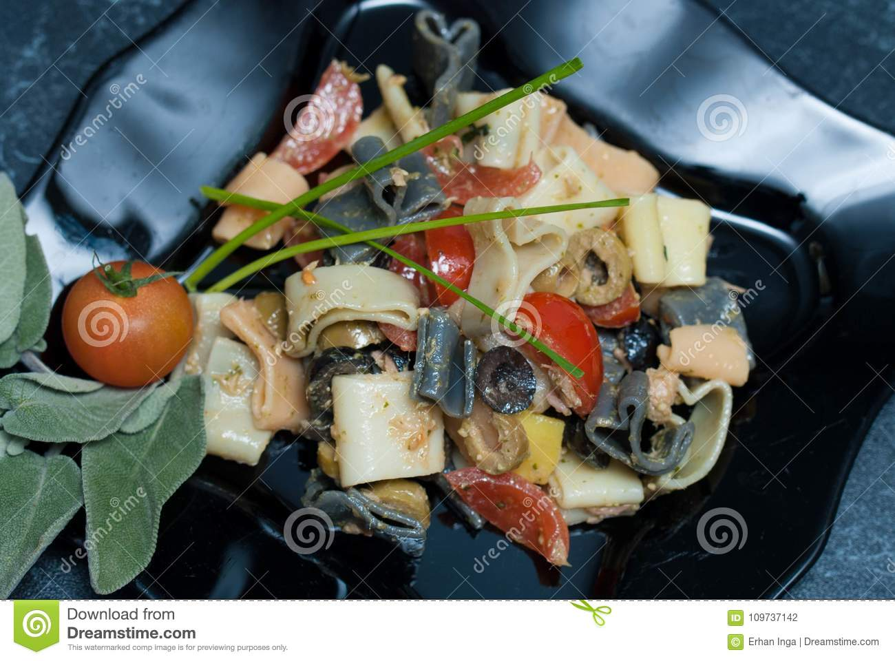 Colorful Pasta Heart-Shaped with Sauce, olivevs, Tomatoes in Black Plate. Top view. food.