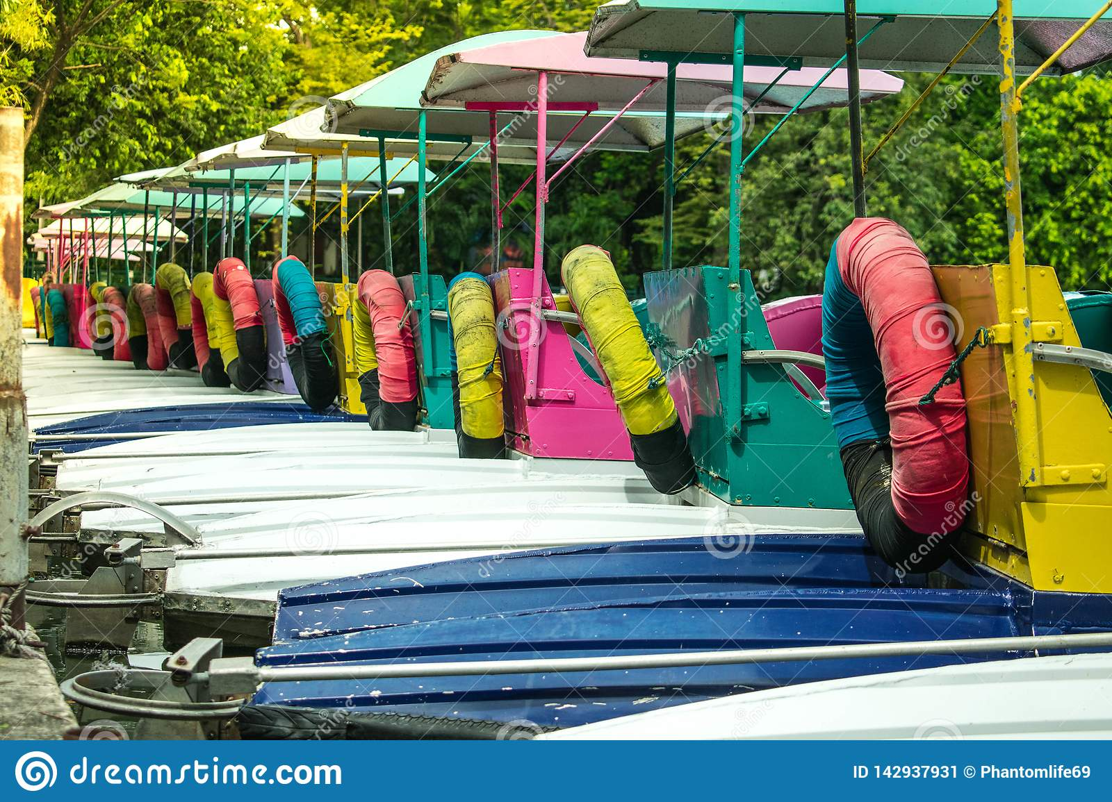 Colorful pedal boats anchor at pier in park.