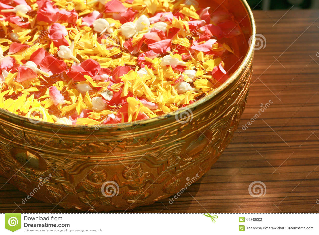 Colorful petals floating on water in golden bowl for pouring on the respected person s hand in Songkran festival