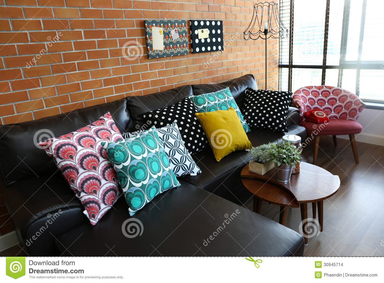 colorful pillows on a sofa with brick wall stock images - image