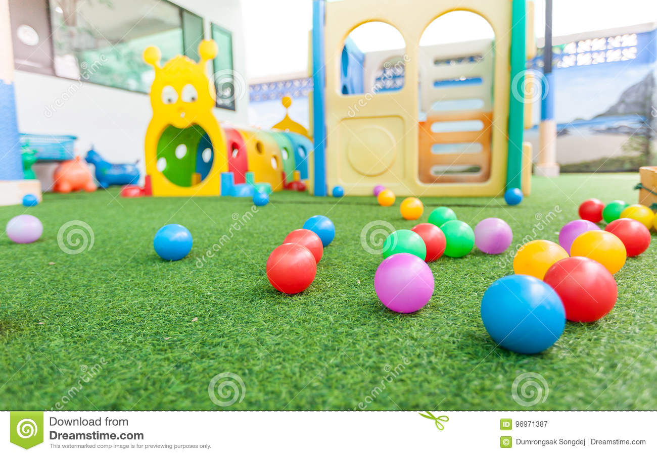 Colorful plastic ball on green turf at school playground