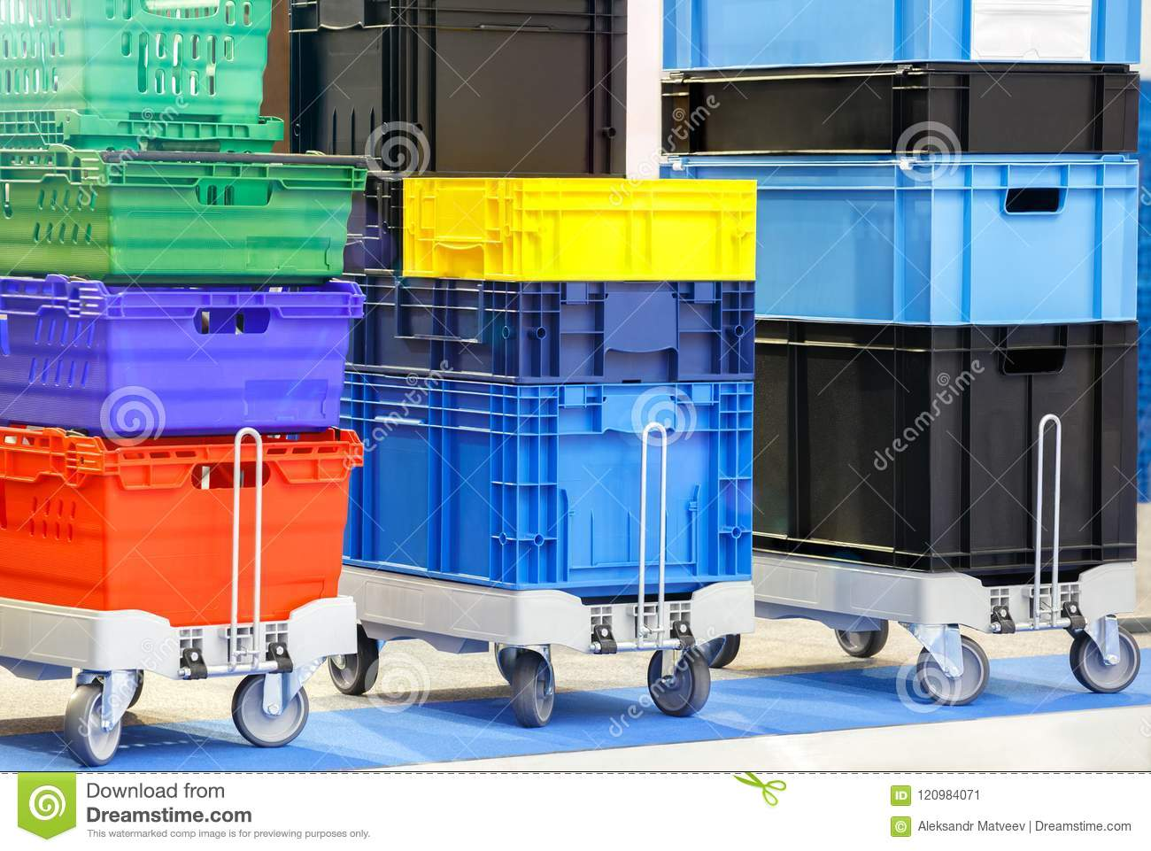 Colorful plastic boxes stacked one upon the other on warehouse trolley or platform trolley