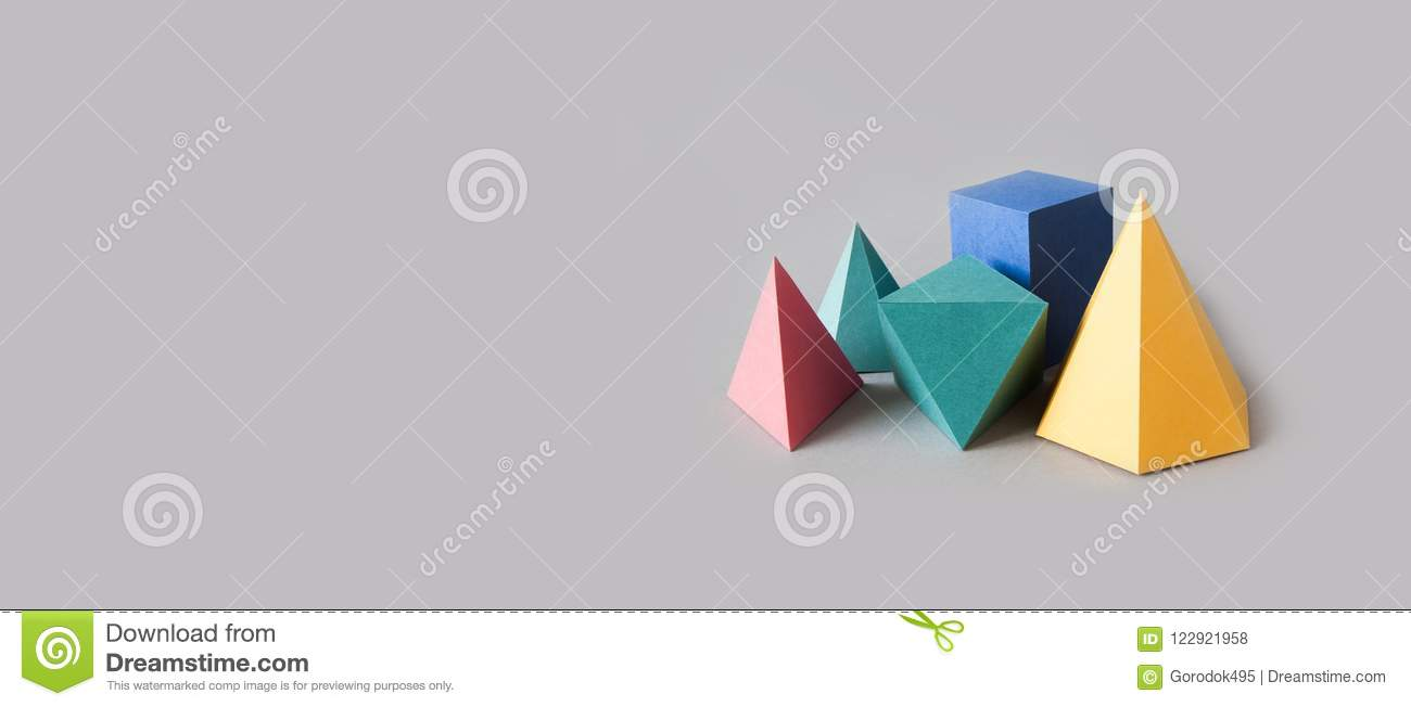 Colorful platonic solids, abstract geometric figures on gray background. Pyramid prism rectangular cube yellow blue pink
