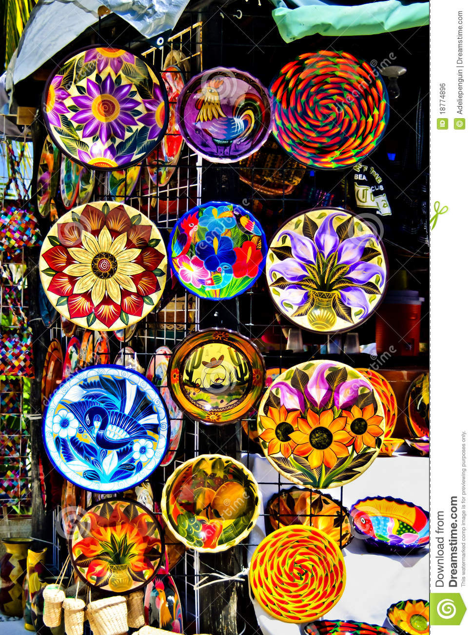 Brightly painted colorful ceramic plates hang on a stall in a crafts ...