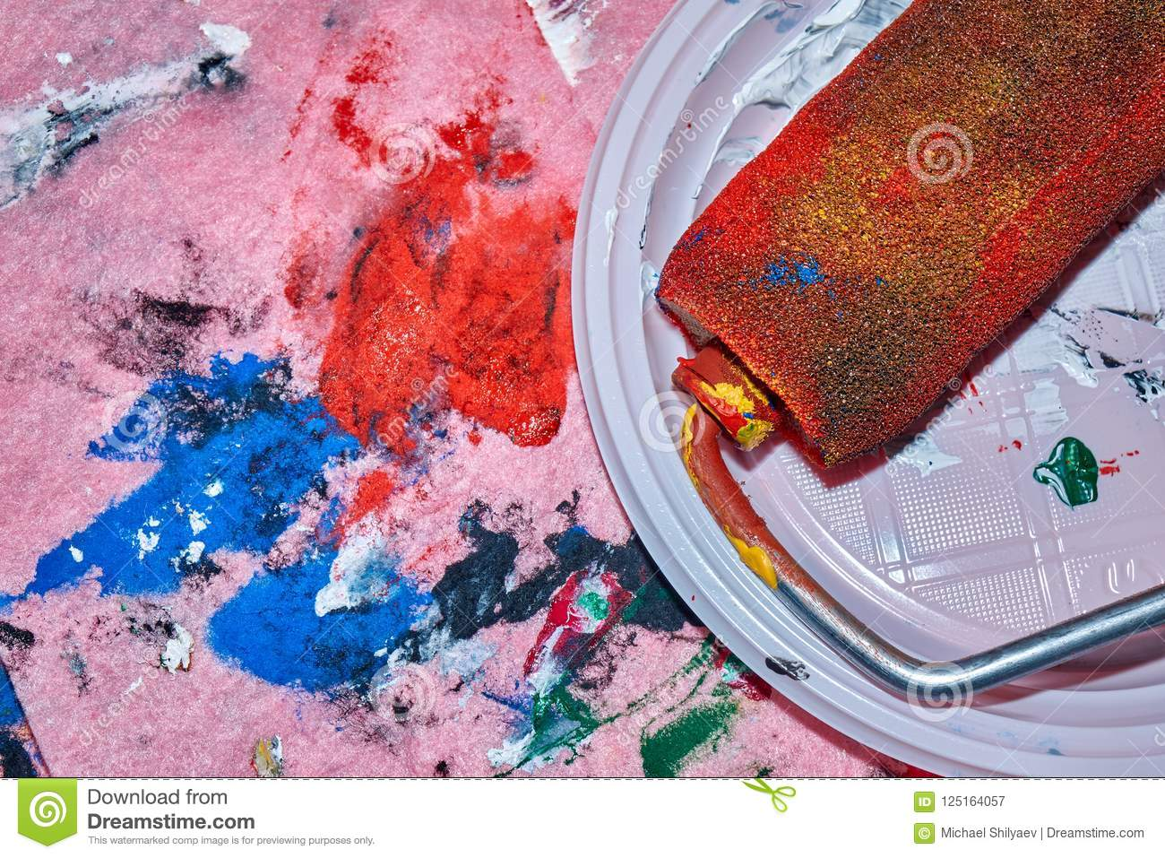 Colorful roller lying on the white plate after beign used for wall art painting