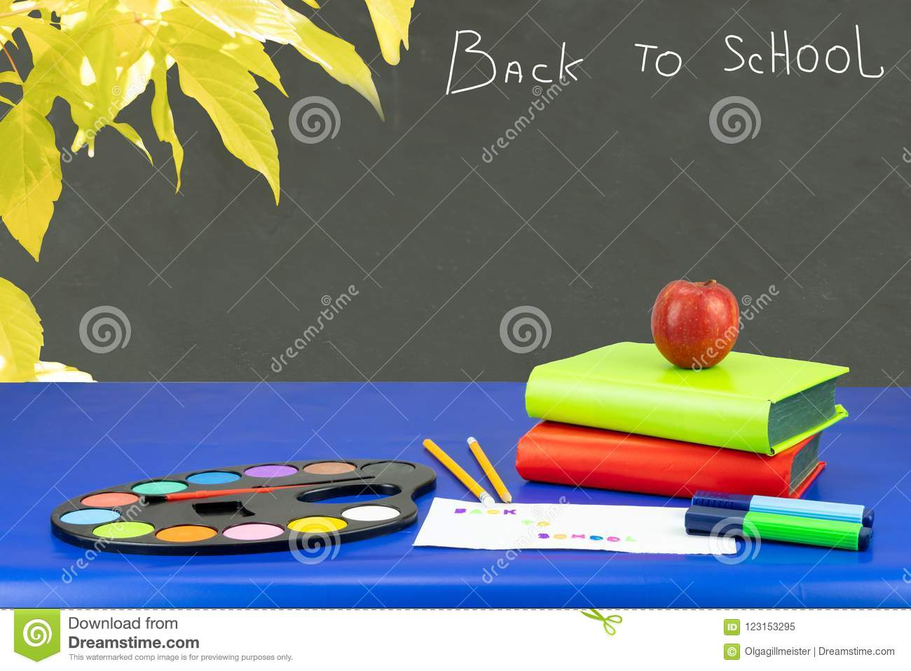 Colorful school equipment and two books on dark blue table again