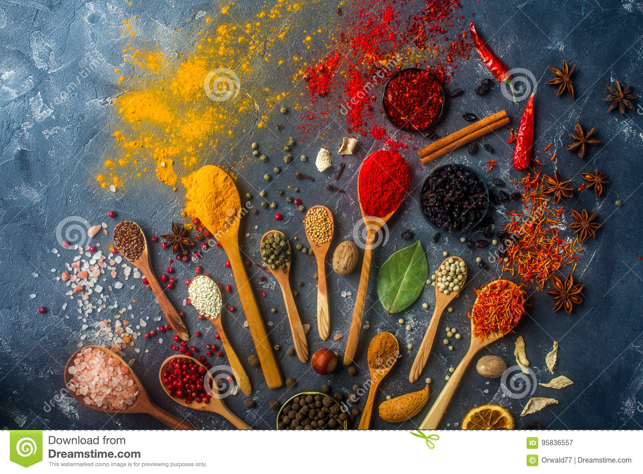 Colorful spices in wooden spoons, seeds, herbs and nuts on dark stone table.