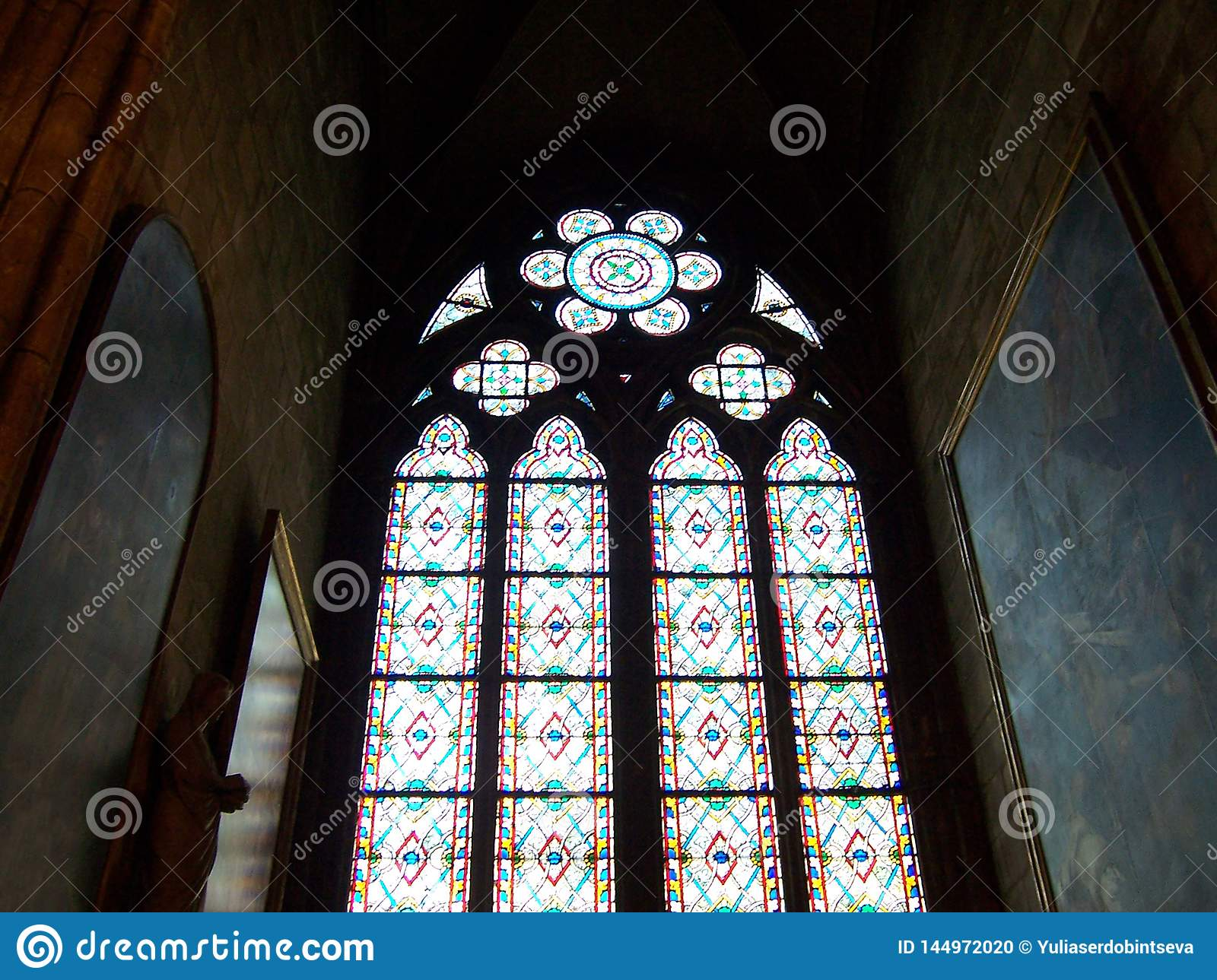 Paris, France - August 06, 2009: Colorful stained glass window in dark interior of the Notre Dame de Paris cathedral