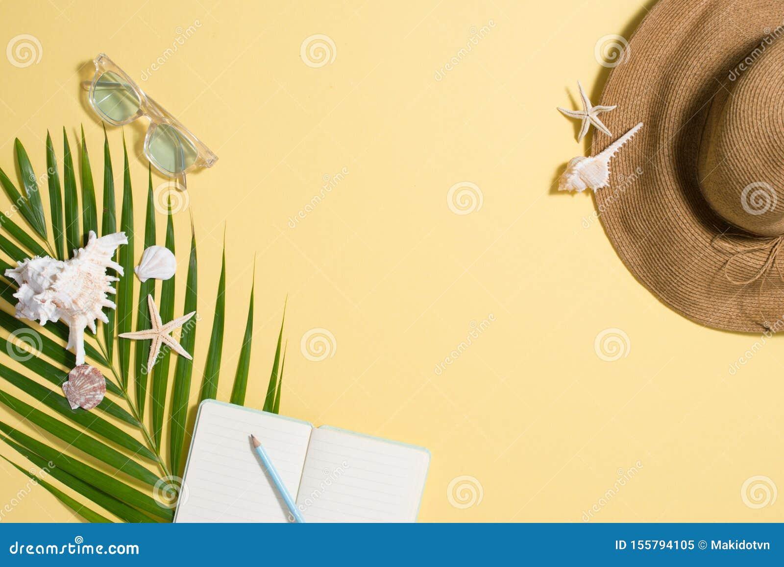 Colorful summer holidays fashion flat lay - straw hat, sunglasses, sea shells on bright yellow background