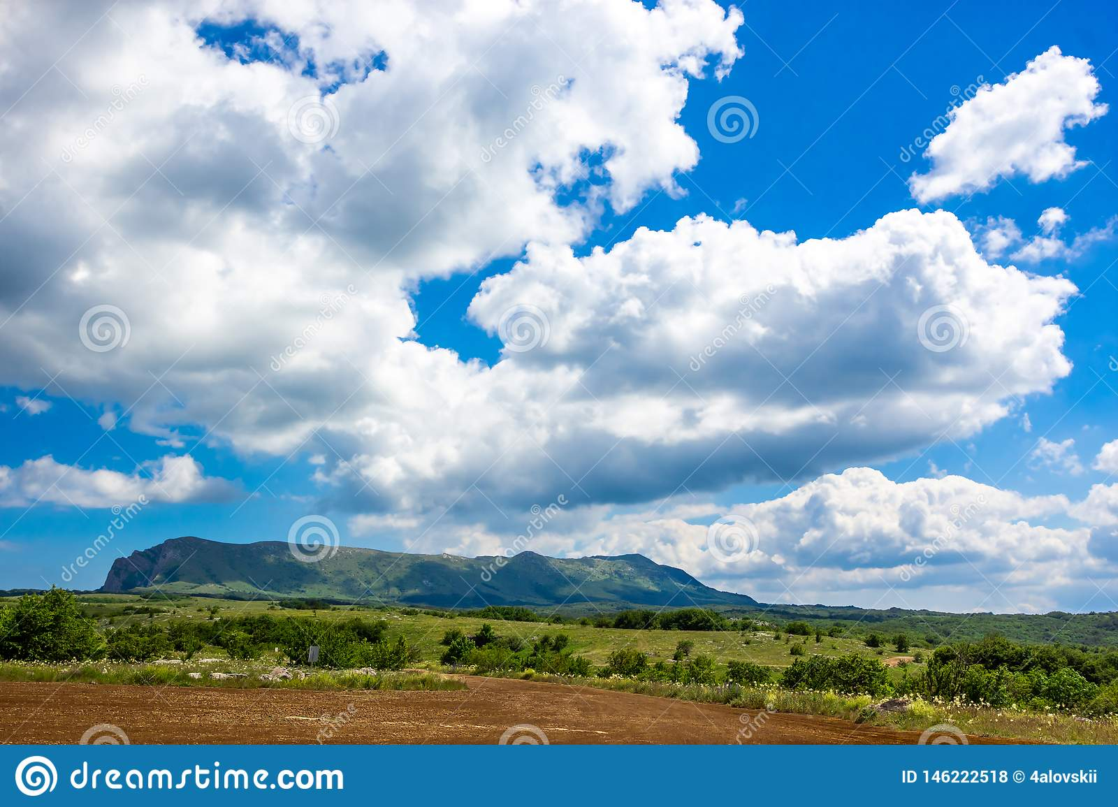Colorful summer landscape in the mountains, under a blue sky with white clouds