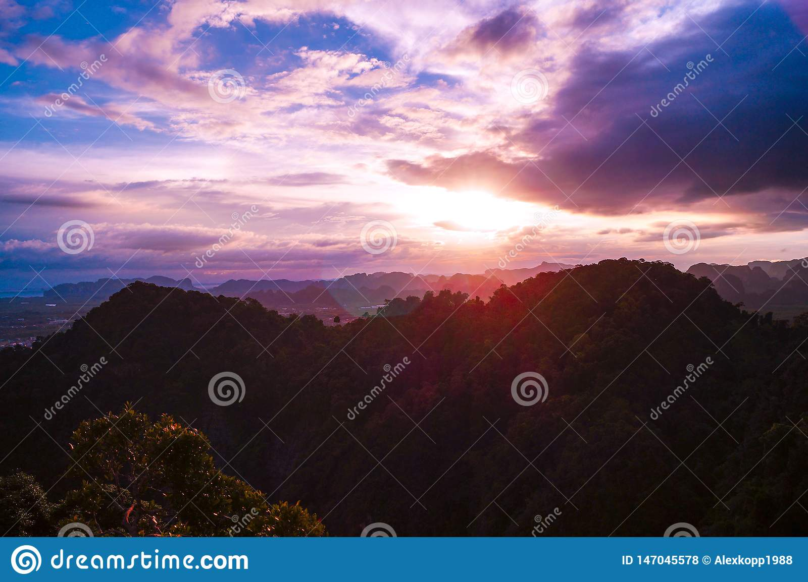 A colorful sunset with a beautiful view from the Tiger Cave Mountain over the mountains of Krabi, Thailand