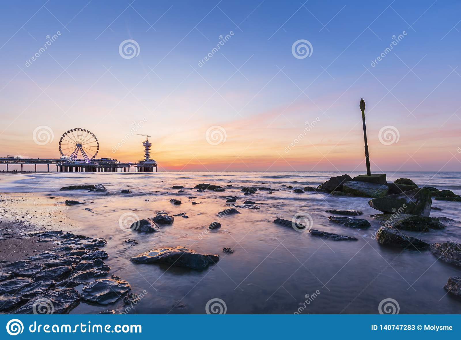 Colorful sunset on coastline, beach, pier and ferris wheel, Scheveningen, the Hague