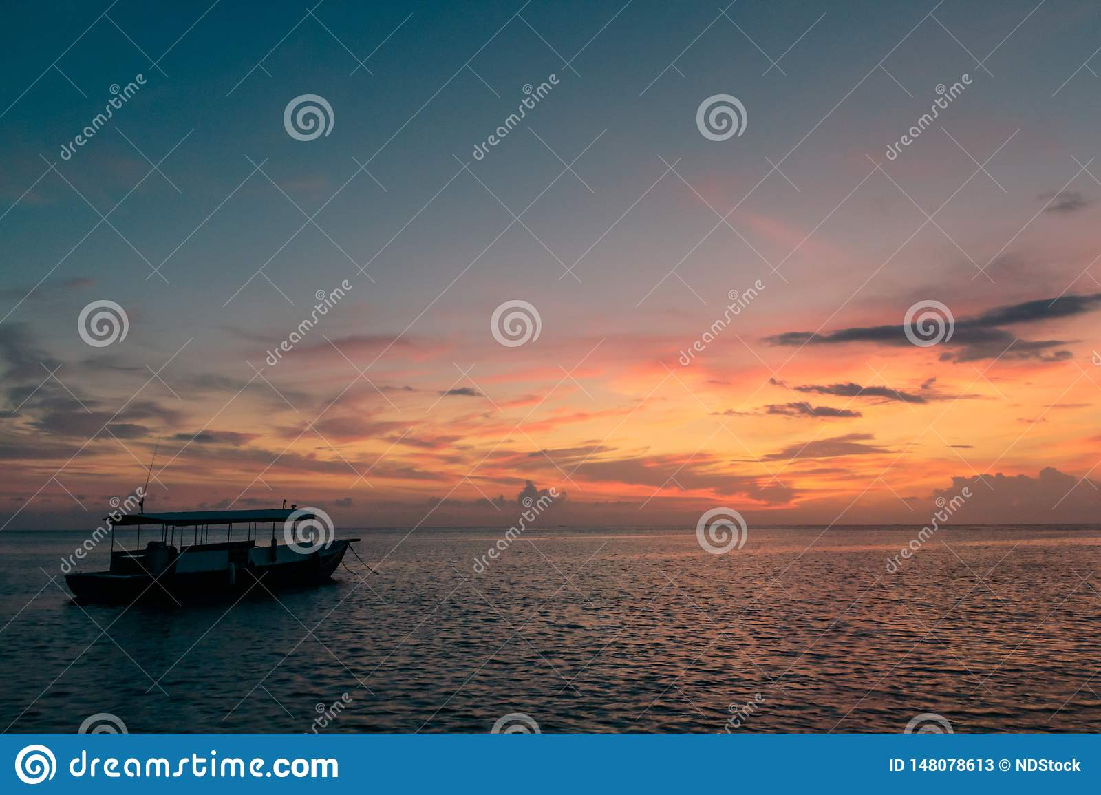 Colorful sunset reflection on a cloudy sky and sea. little boat on the ocean