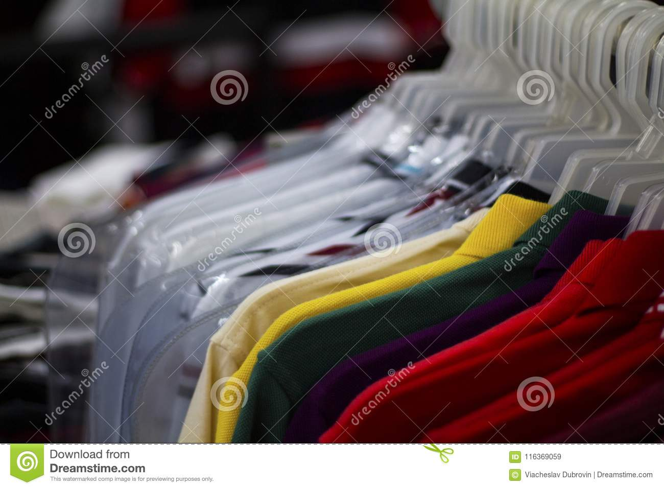 884b032329c Colorful t-shirts on hang for sale in shop. Multicolored summer polo on  hanger.