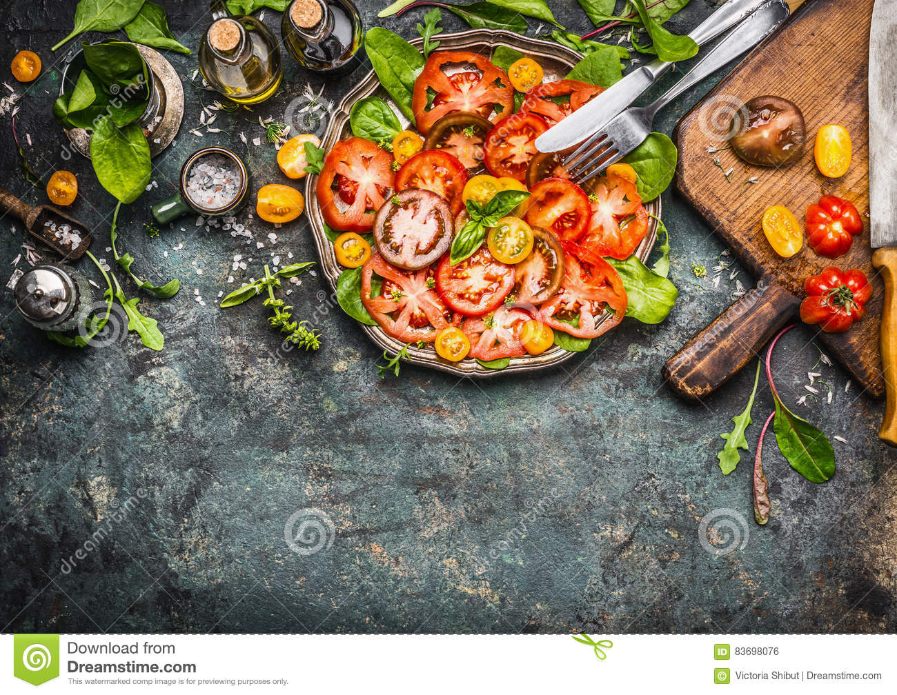 Colorful tomatoes salad preparation with cutting board, plate and cutlery , top view