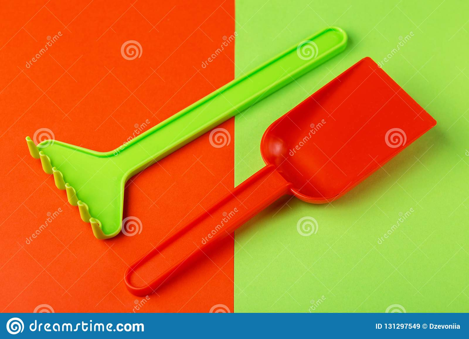 Colorful toy spade and rake on bright background