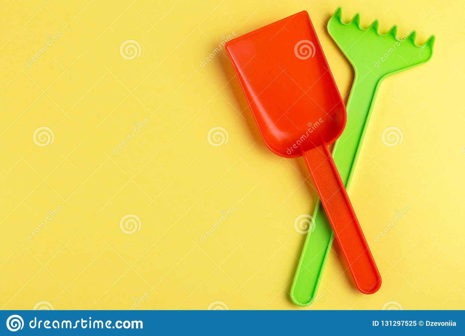 Colorful toy spade and rake on bright yellow background