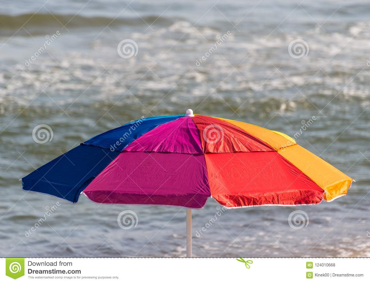 A colorful umbrella spread out on the beach on a beautiful sunny summer day with a rough sea.