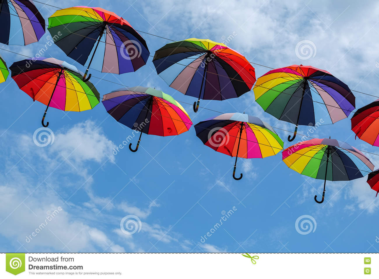 1bb1e4e2d Bright colorful rainbow umbrellas floating against blue sky with copy space