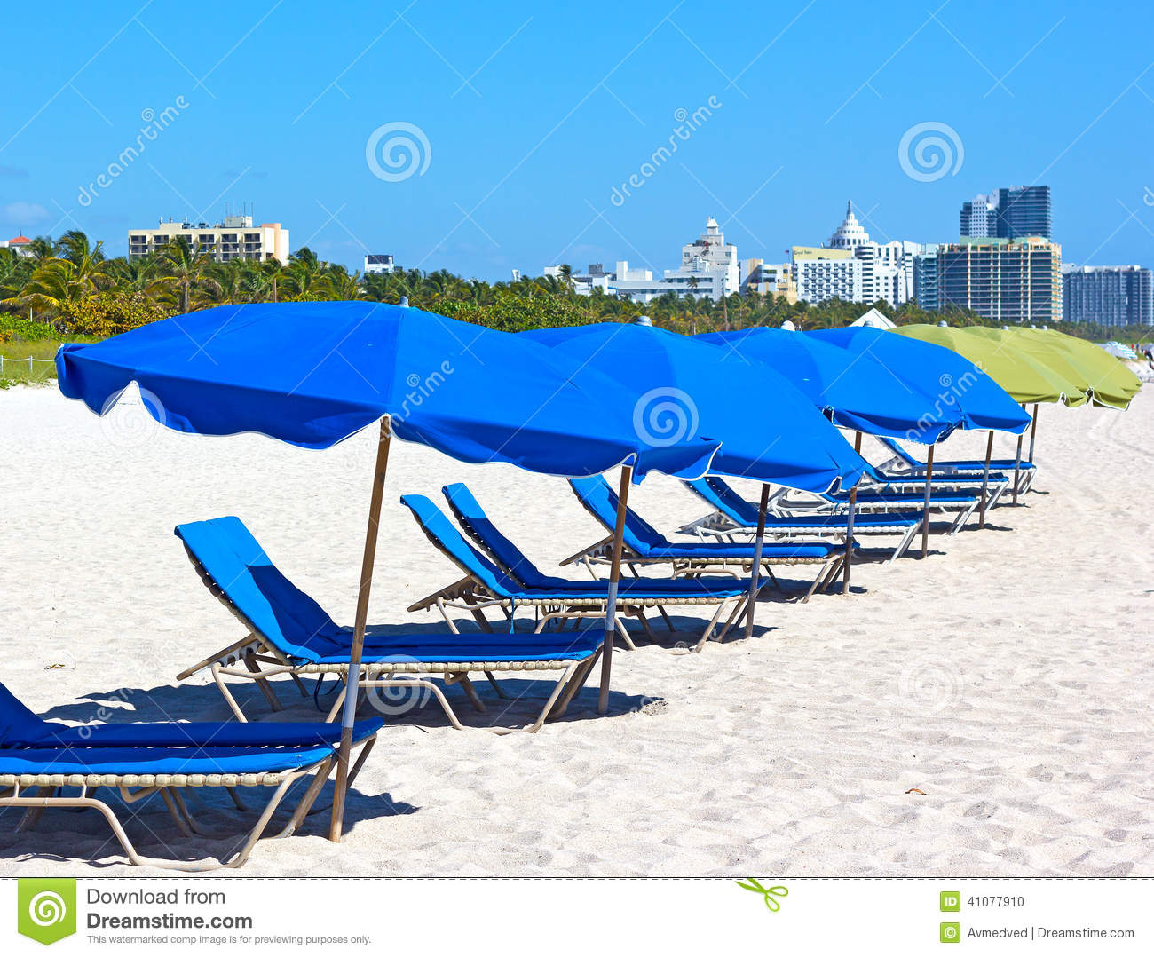 colorful umbrellas and lounge chairs on miami beach with visible