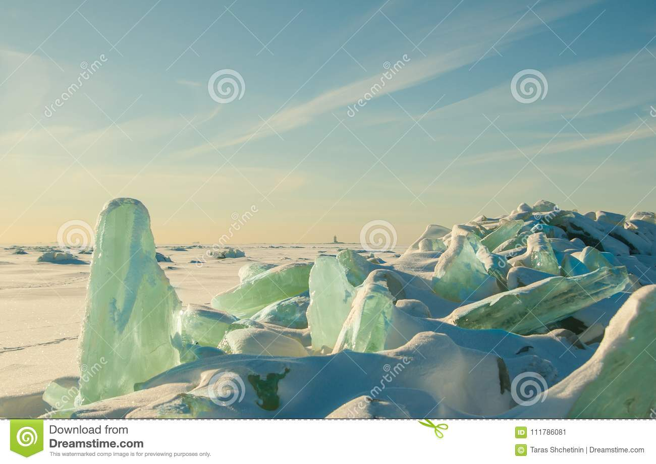 Colorful winter landscape with crystal cracked ice, deserted surface of frozen sea covered by snow and blue sky with cirrus clouds