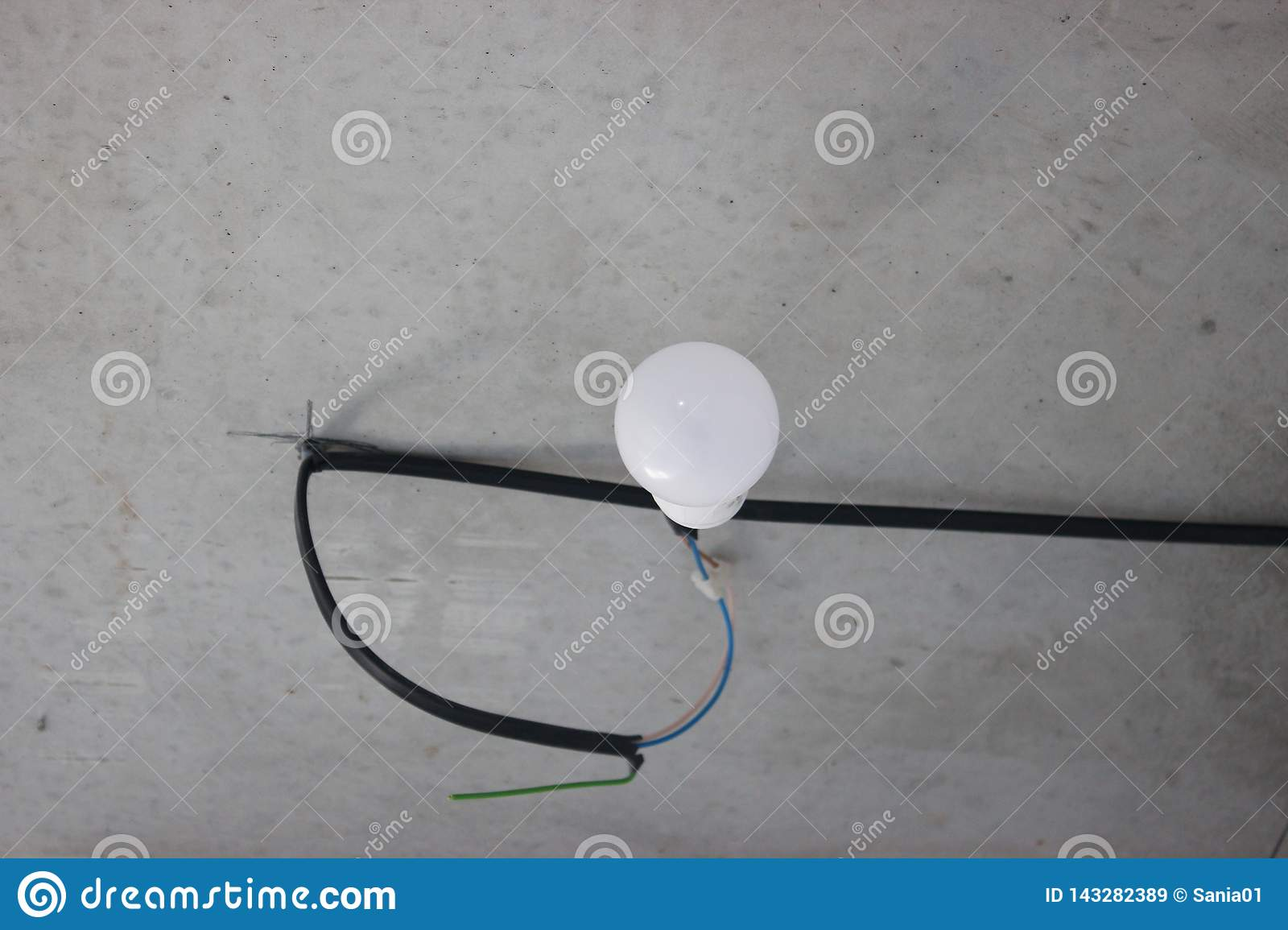 colorful wires sticking out of wall, repair the apartment, house or office  electrical  wiring  light bulb and switch on the background of gray concrete wall