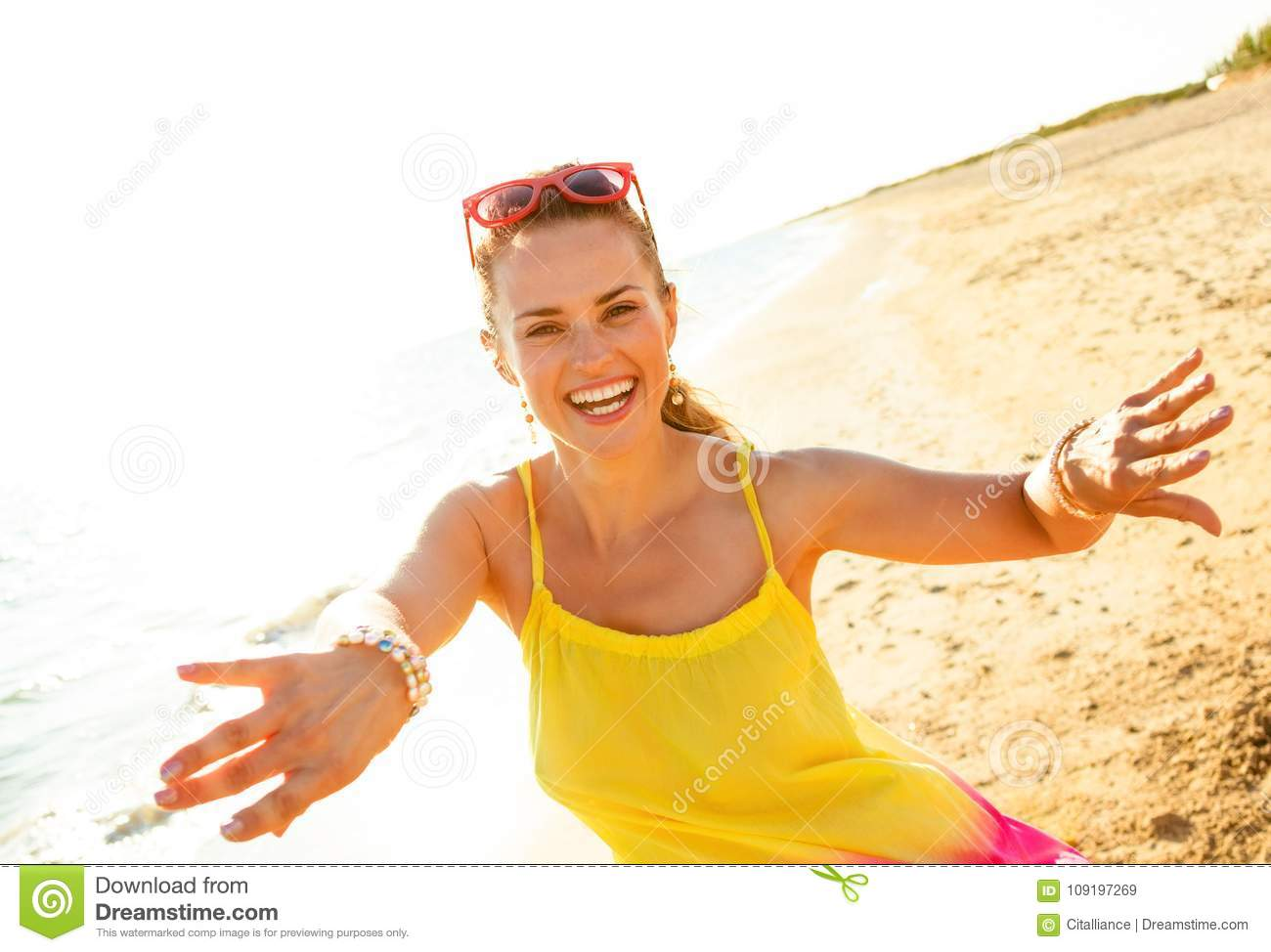 Smiling young woman on beach in evening having fun time