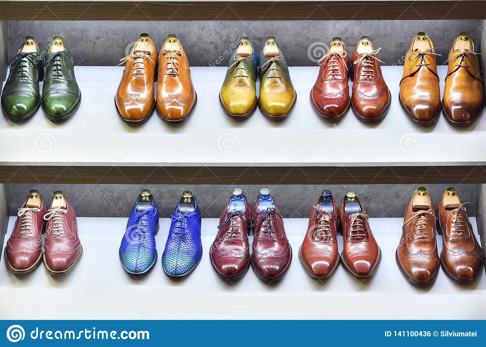 Colorfull pairs of shoes are exposed for sale.