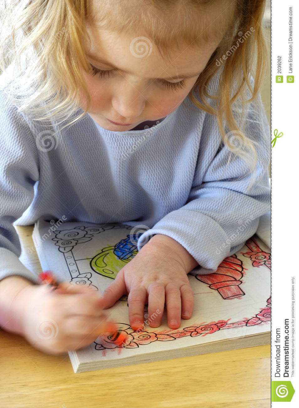 Little child coloring in coloring book with crayons