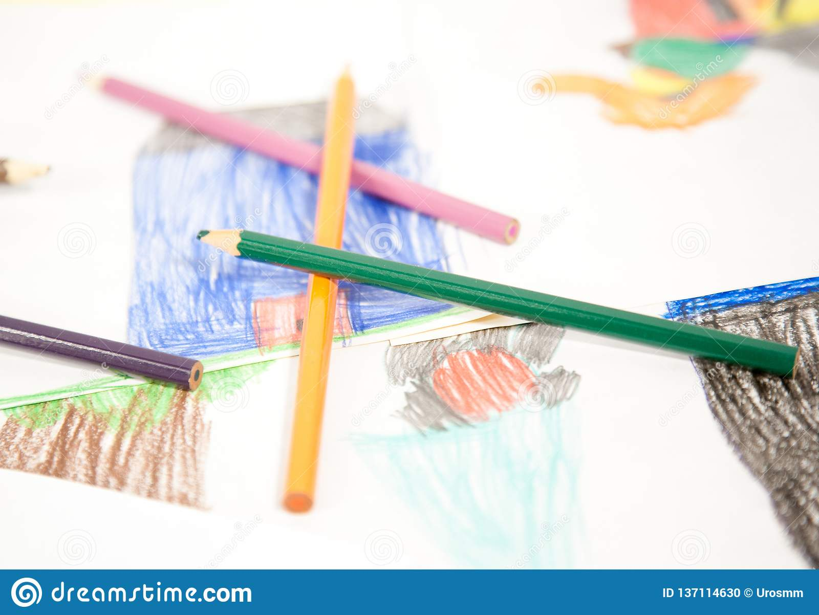 Coloring pencils of all colours on the drawings of a child sharpened with wooden scabs