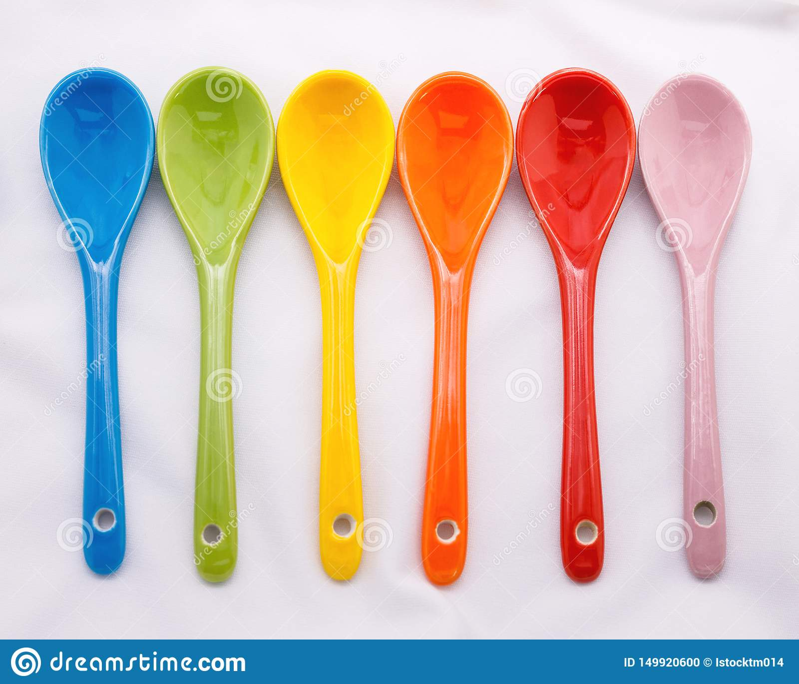 Colors ceramics spoon on white fabric background. Colorful concept