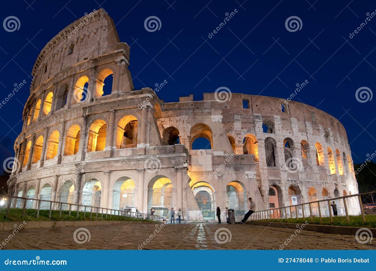 Colosseo och stengata på natten i Rome - Italien