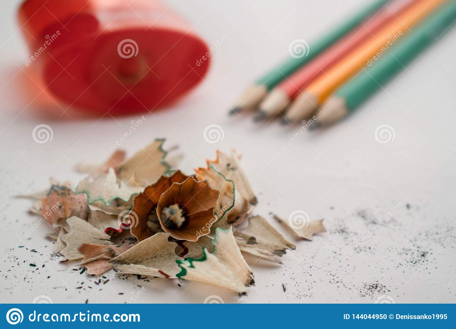 Colour pencils pile of sawdust and red sharpener on a white background