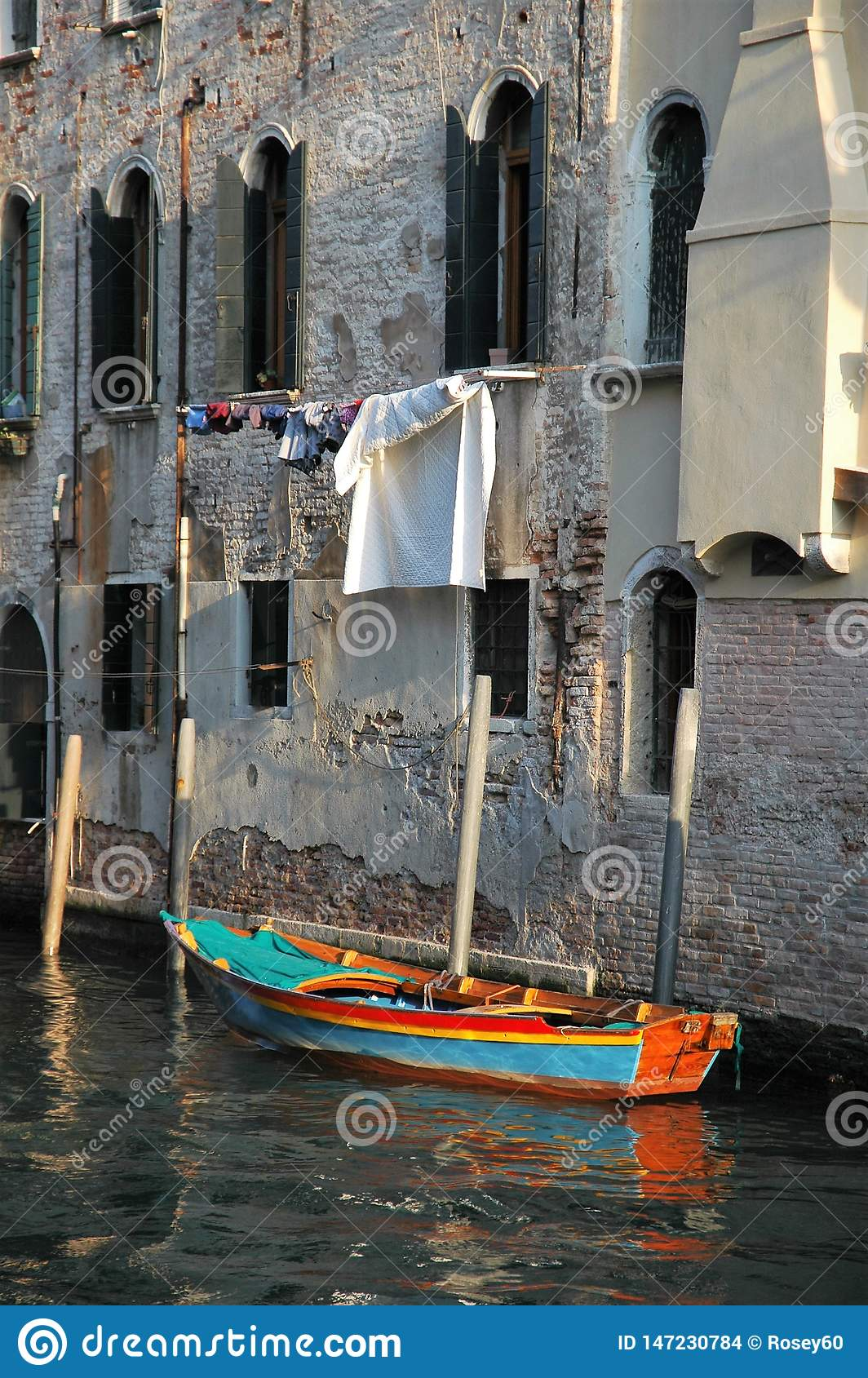 Colourful boat tied to old building with washing hanging in background.