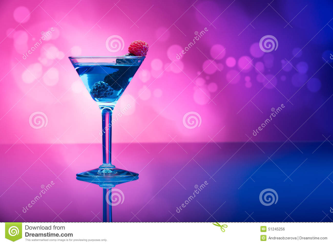 Colourful cocktails garnished with berries, background with light effects