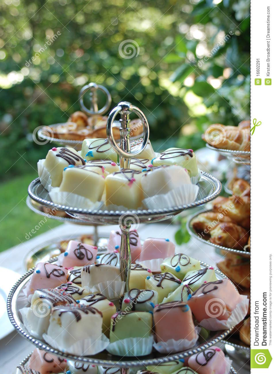 Colourful Petit Fours On A Cake Stand With Bokeh Stock