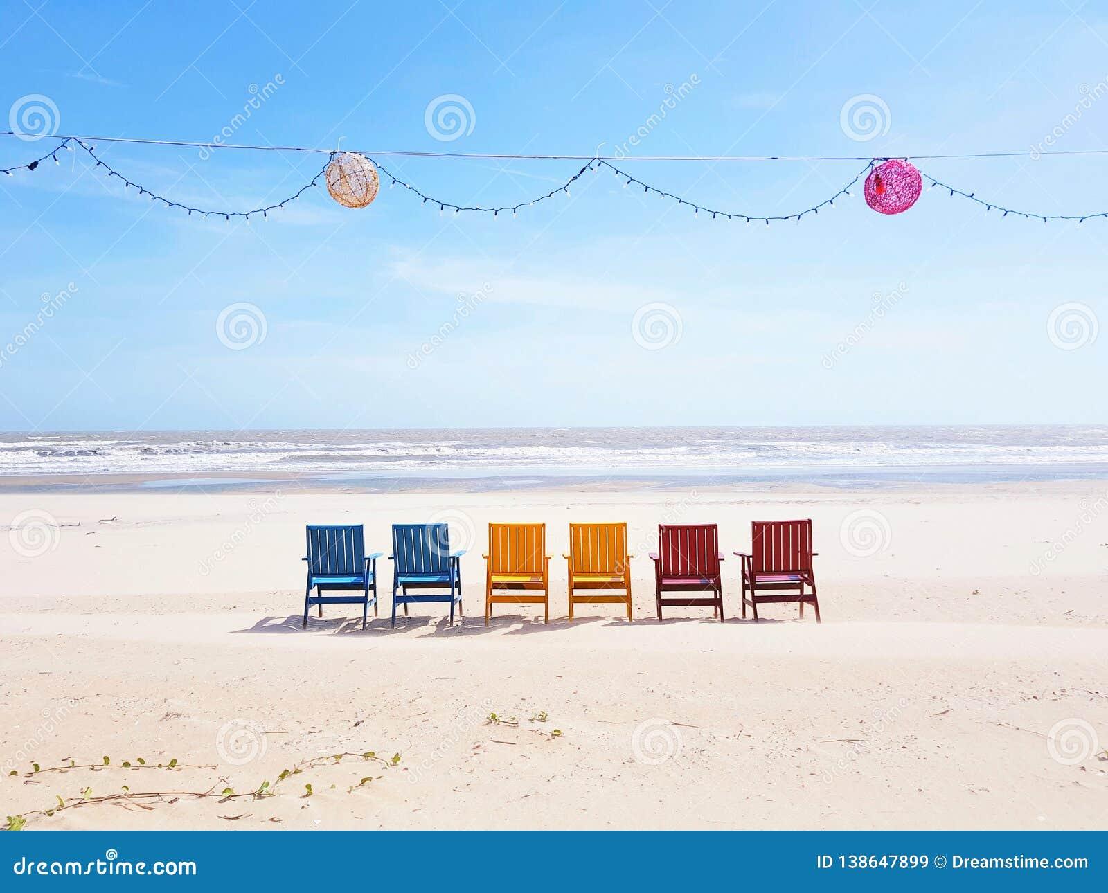 Colourful plażowi krzesła na szerokim białym piasku wyrzucać na brzeg stawiać czoło ocean w Wietnam z lampions i lekkim łańcuchu
