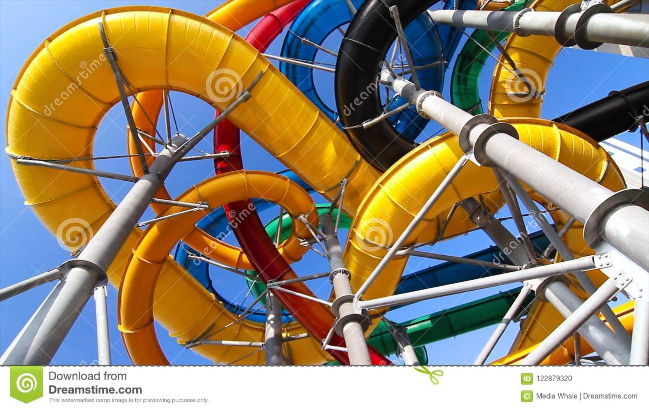 Colourful plastic slides in aquapark in the sunlight. Scene. Bottom view of the water slides