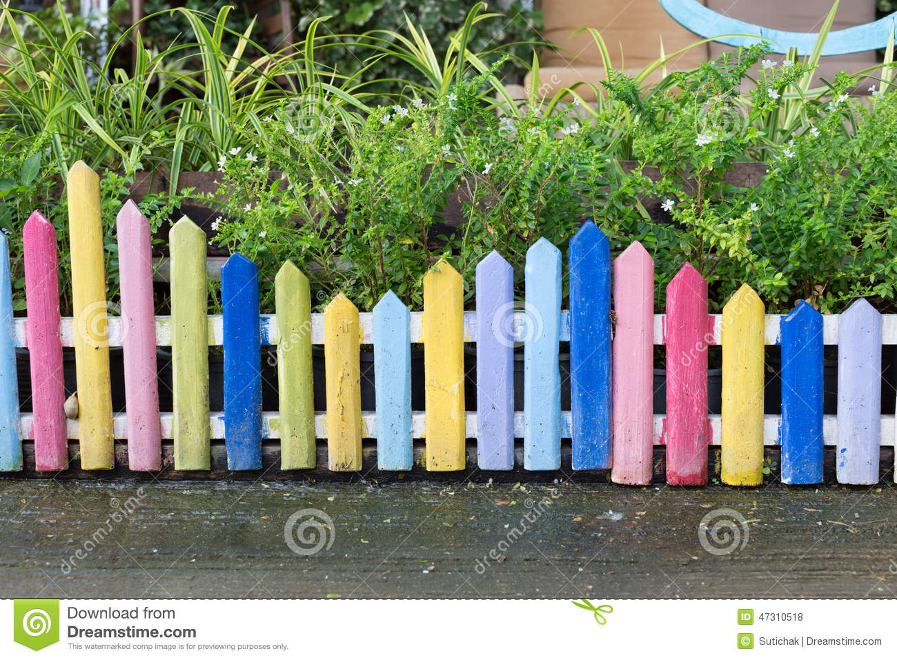 Colourful wood fence in small garden stock photo image for Short garden fence designs