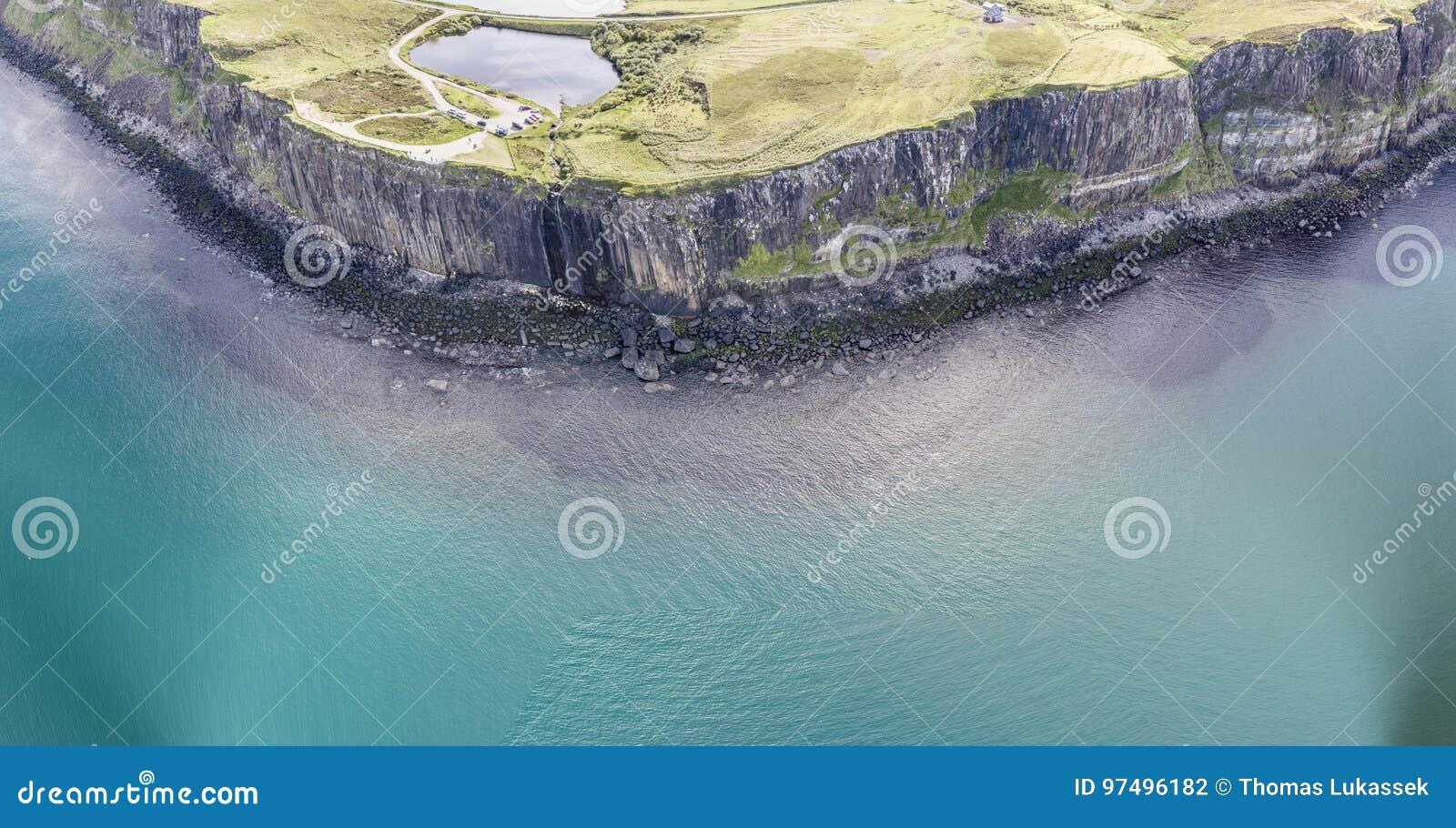 Colpo aereo cinematografico della linea costiera drammatica alle scogliere vicino alla cascata famosa della roccia del kilt, Skye