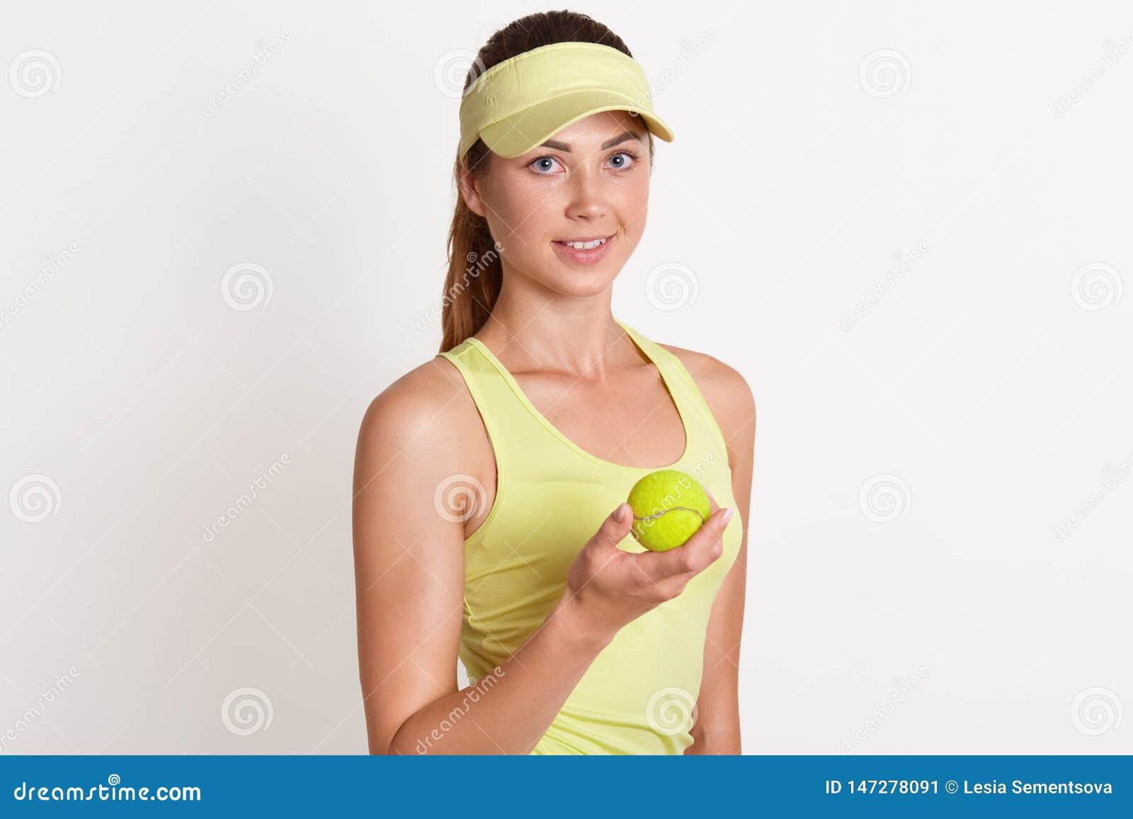 Colpo dell interno dello studio di giovane fondo bianco controllante femminile magnetico positivo snello, tenente tennis giallo l