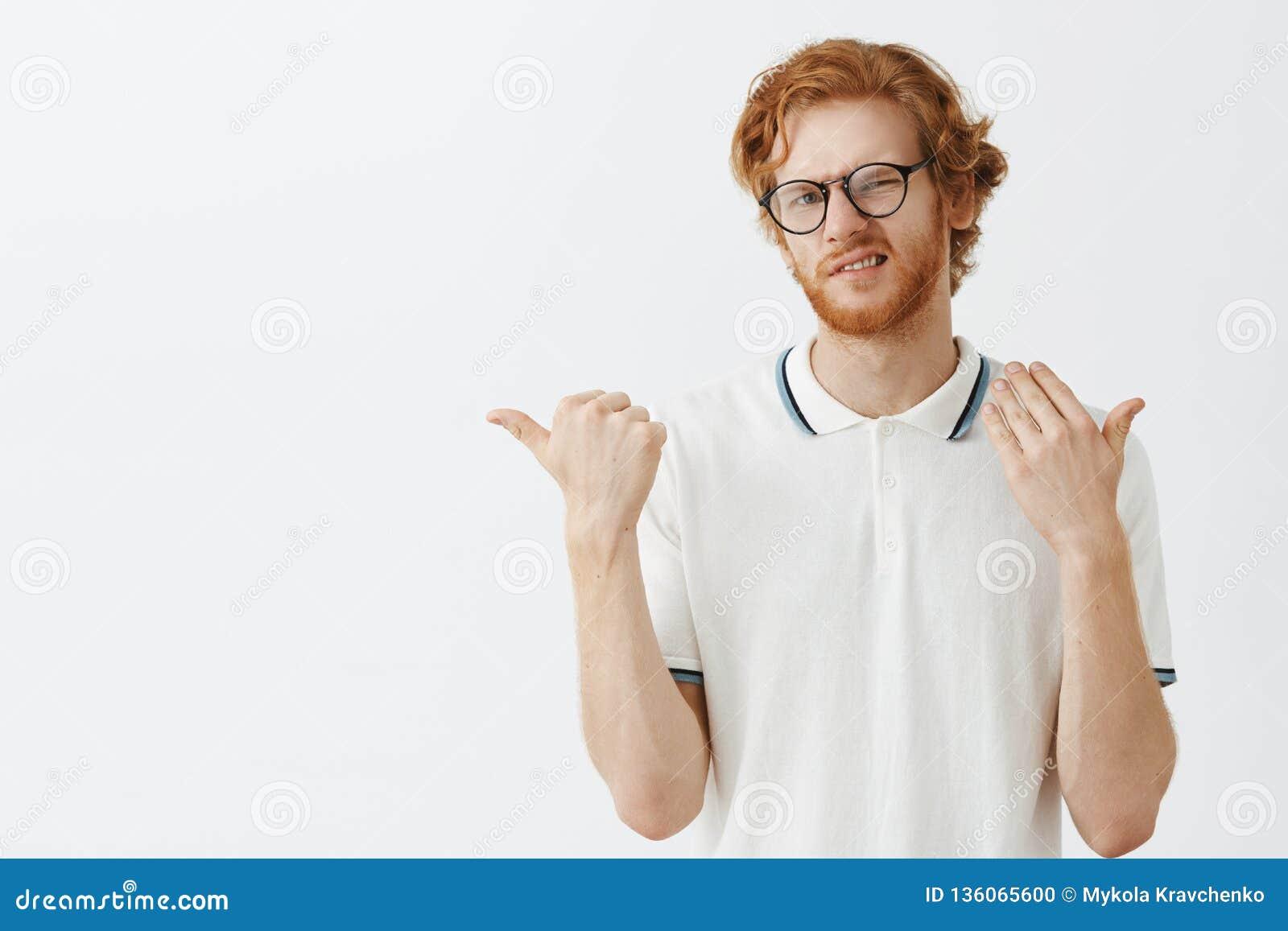 Colpo dell interno di giovane maschio della testarossa dispiaciuta ed incerta con la barba in occhiali neri che sono strabico e c