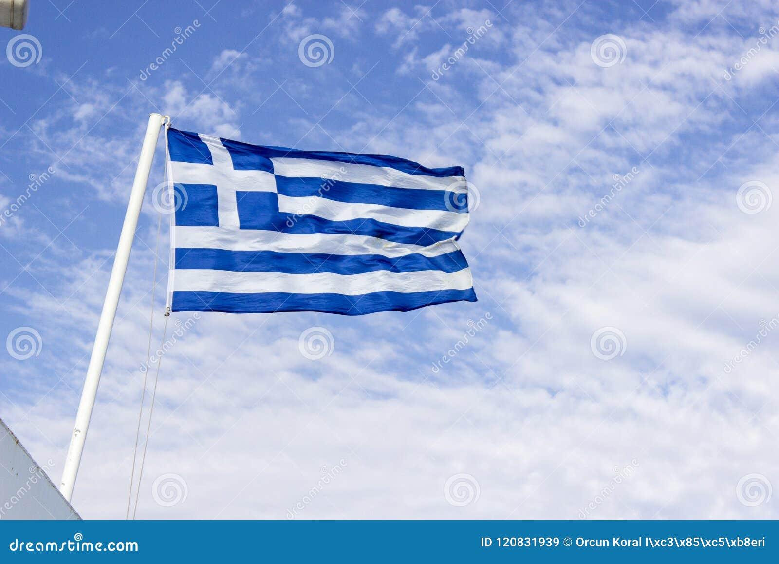 Colpo inferiore anteriore della bandiera d ondeggiamento variopinta della Grecia con il fondo blu del cielo aperto a Smirne in Tu