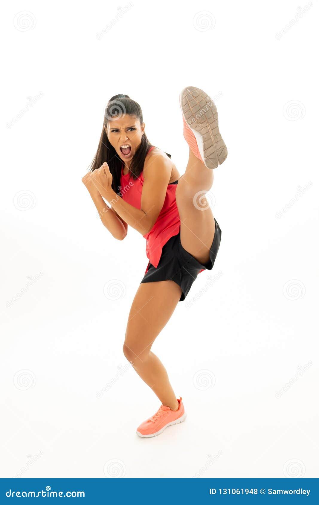 Colpo integrale dell atleta della donna di misura che esegue uno stile marziale di karatè di alta scossa