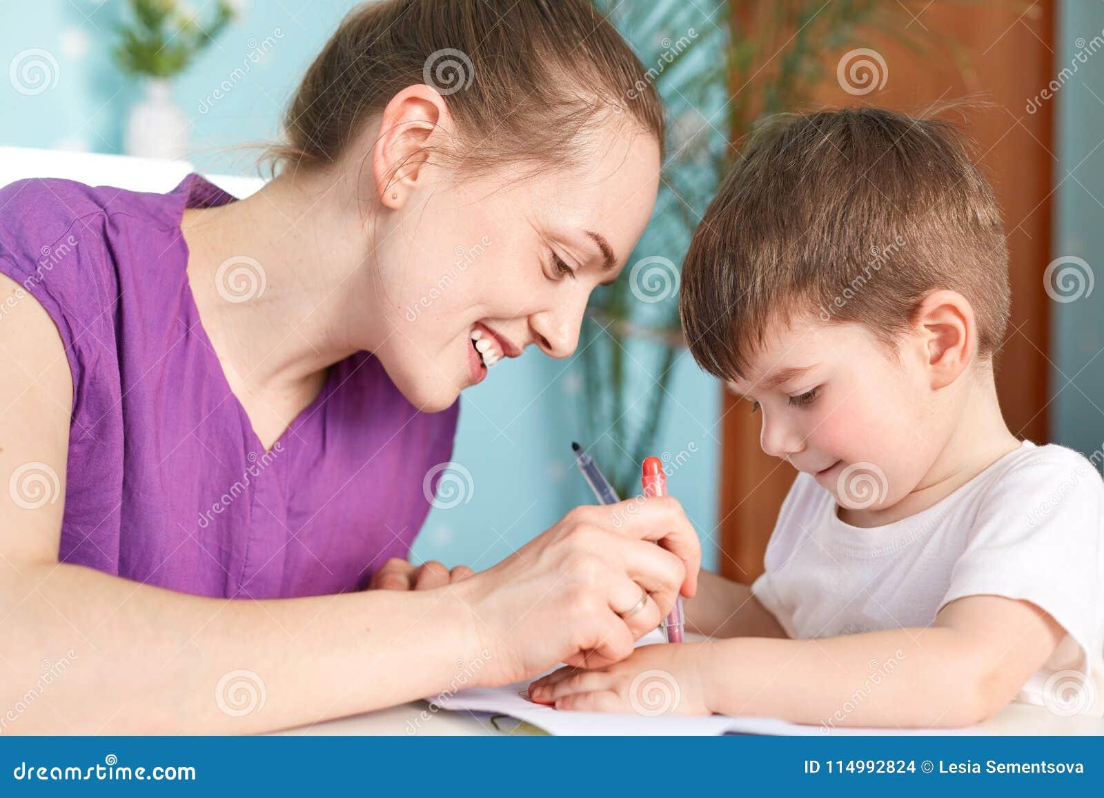 Colpo orizzontale di giovane madre sorridente felice che è felice di passare tempo libero con il suo piccolo figlio, tiraggio qua