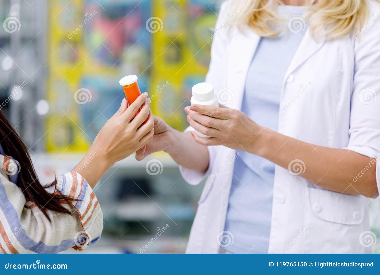 Colpo potato dei contenitori della tenuta del cliente e del farmacista con il farmaco